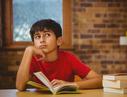 Thoughtful boy reading book in library